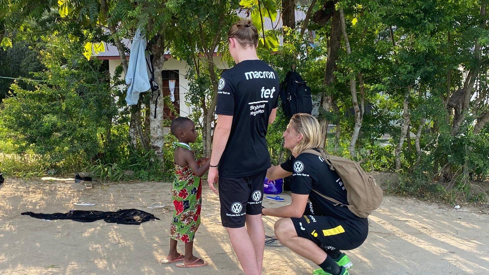 Mikael og Erlend møter en liten gutt på besøk hos en familie i Tanzania.