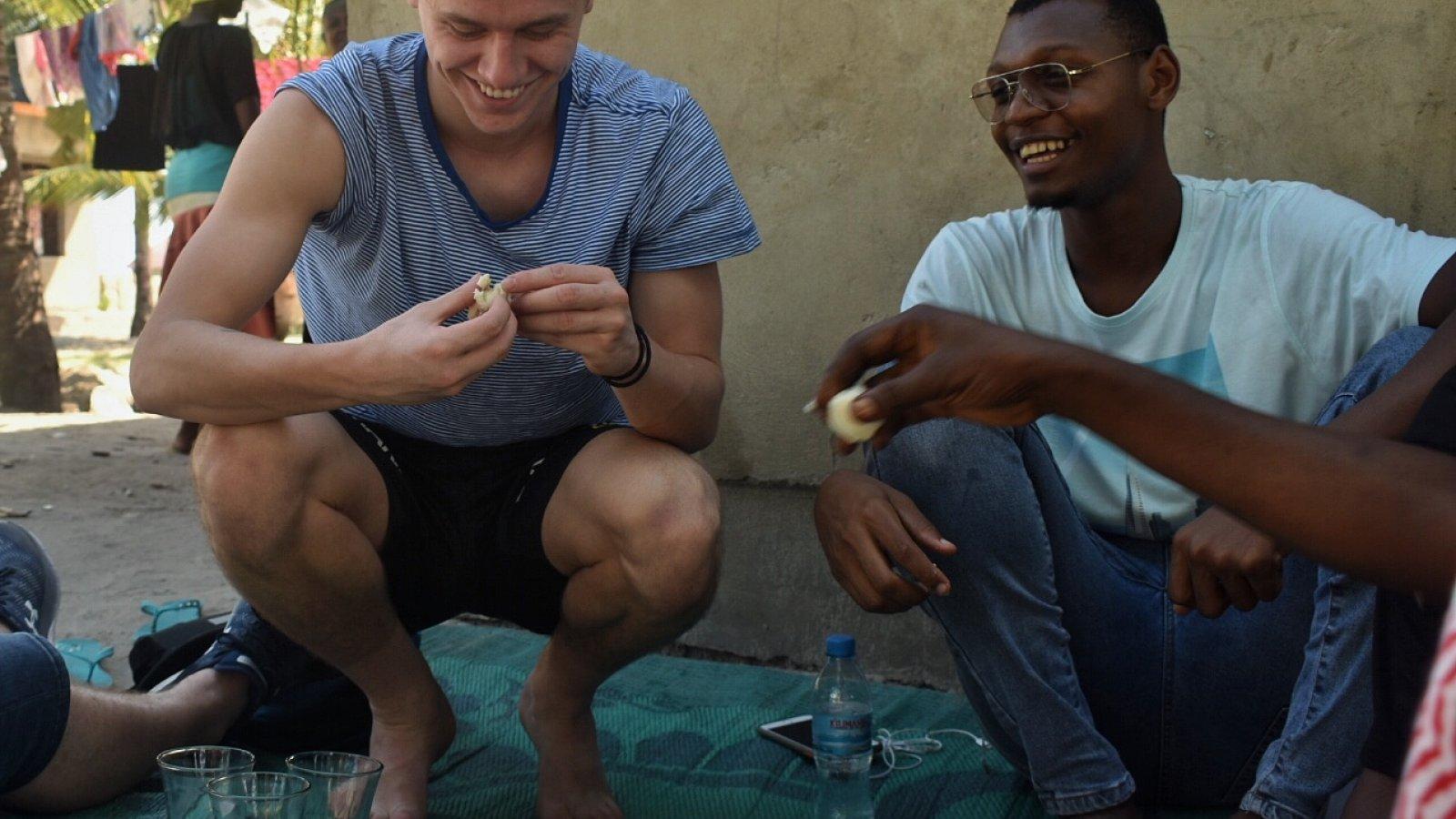 Mikael på middagsbesøk hos en familie. Måltidet ble spist ute, på et teppe på bakken. Familien bodde på ett rom, men de var heldige som delte utedo og brønn med naboene i landsbyen.